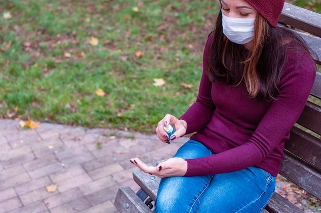 Conceito covid-19. mulher com máscara médica, lavando as mãos com álcool gel desinfetante. proteção e prevenção contra coronavírus.