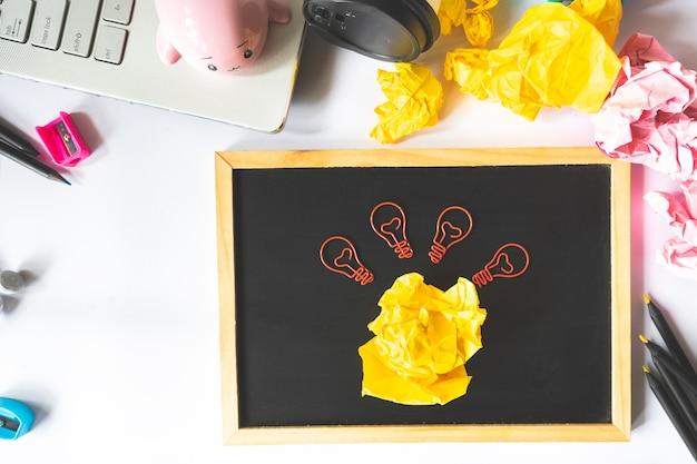 Conceito criativo com bola de papel amassado e clipe de papel de lâmpada, laptop e lápis