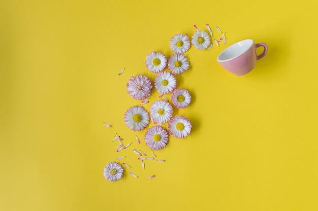 Conceito criativo com uma xícara rosa e flores sobre fundo amarelo
