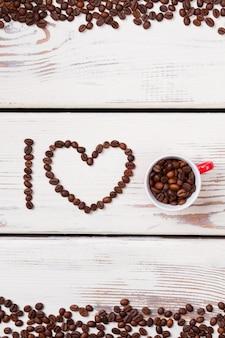 Conceito criativo da frase eu amo café feito de feijão. grãos de café torrados em forma de coração. pranchas de madeira brancas.