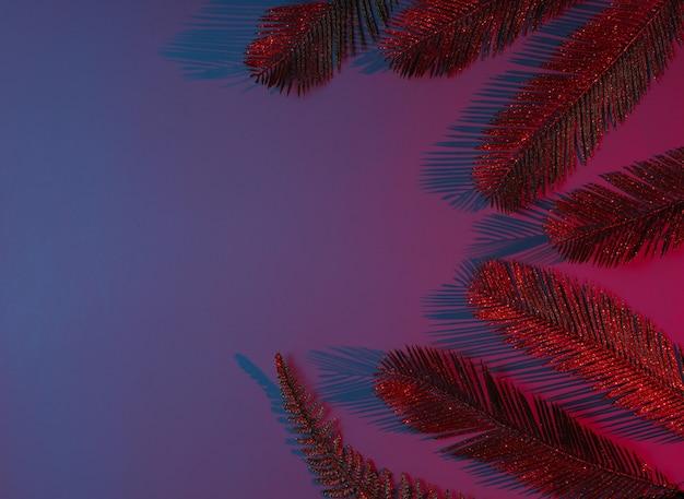 Conceito criativo de arte pop tropical. folhas de palmeira douradas sobre fundo gradiente de néon vermelho-azulado.