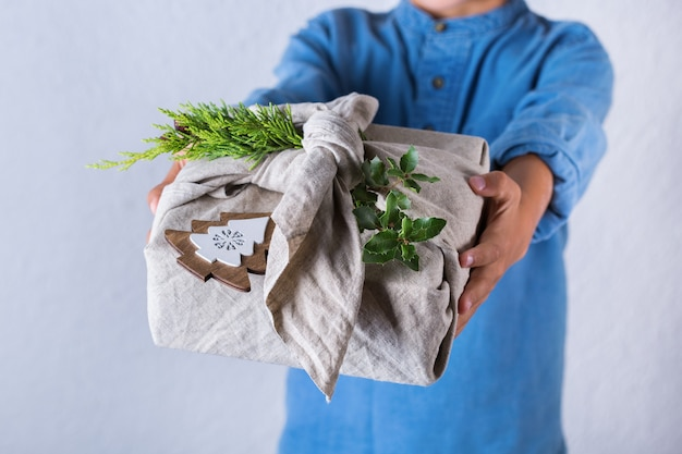 Conceito criativo de desperdício zero de natal. caixa de presente feita à mão em um embrulho feito à mão em tecido furoshiki ecológico de estilo japonês tradicional