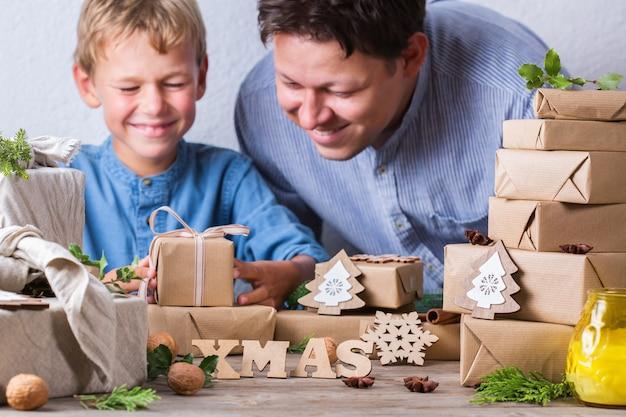 Conceito criativo de desperdício zero de natal. feliz menino bonito e seu pai embrulhando caixas de presente em papel artesanal eco friendly e tecido furoshiki tradicional estilo japonês. tempo para a família em casa