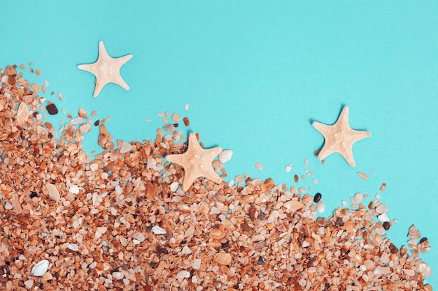 Conceito criativo de praia mínimo. areia e estrelas do mar em fundo colorido de hortelã. plano de verão