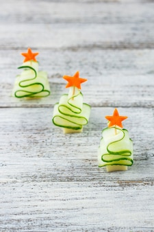 Conceito criativo definiu árvores de natal de pepino, queijo e estrela de cenoura. comida de crianças engraçadas para festa de ano novo em fundo cinza com espaço de cópia
