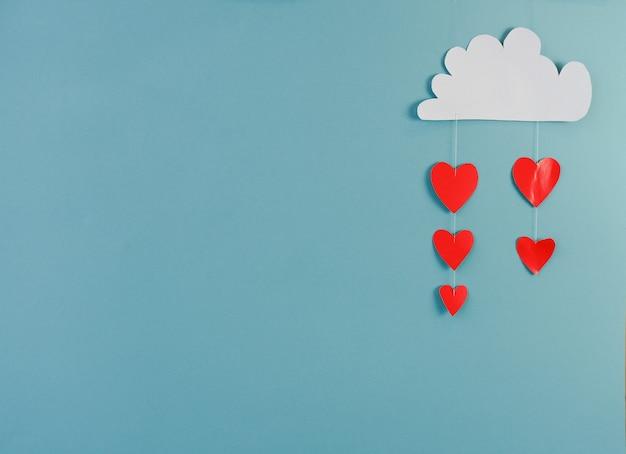Conceito criativo feriado dia dos namorados amor foto de nuvem de papel artesanal chovendo com corações sobre fundo azul.