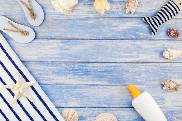 Conceito criativo plano leigo de férias viagens de verão. vista superior da toalha de praia garrafa de protetor solar flip-flops conchas do mar estrela do mar pastel de pranchas de madeira azul com texto de modelo de cópia de espaço