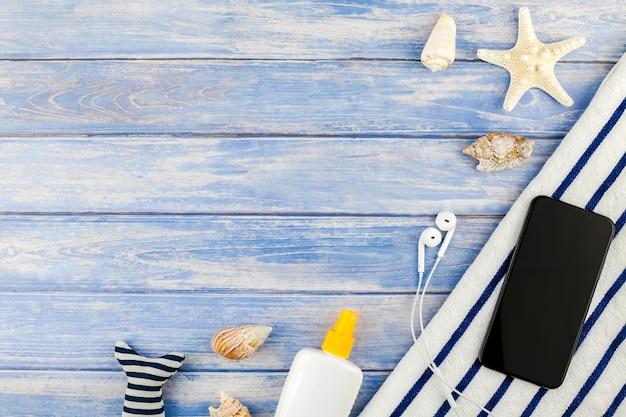 Conceito criativo plano leigo de férias viagens de verão. vista superior da toalha de praia para smartphone conchas estrela do mar em fundo de pranchas de madeira azul pastel com modelo de cópia de espaço para texto