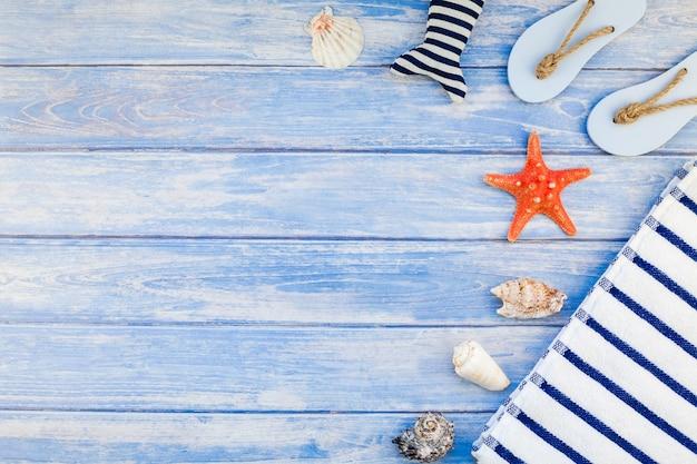 Conceito criativo plano leigo de férias viagens de verão. vista superior de toalha flip-flops, conchas e estrelas do mar em fundo de pranchas de madeira azul pastel com espaço de cópia em texto de modelo de quadro de estilo rústico