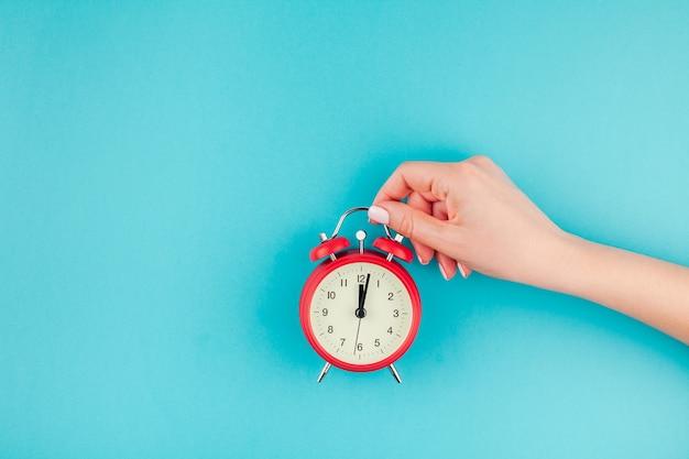Conceito criativo plano leigo vista superior da mão de uma mulher segurando o despertador vermelho vintage em azul turquesa brilhante