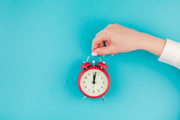Conceito criativo plano leigo vista superior de mulher com a mão em uma camisa branca segurando o despertador vermelho vintage em azul turquesa brilhante