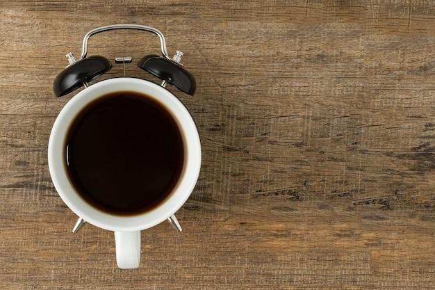 Conceito criativo, uma xícara de café e um despertador vintage preto