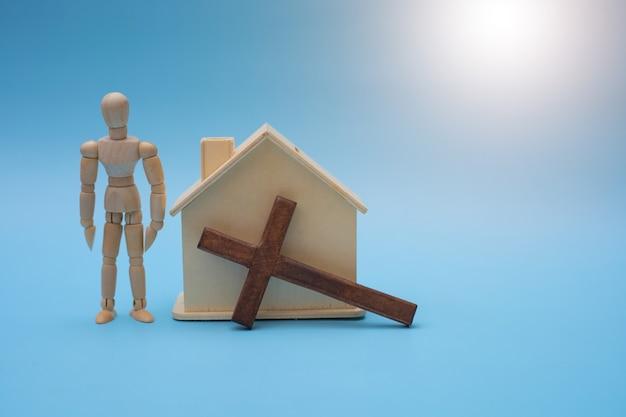 Conceito cristão com cruz de madeira, casa de madeira e pessoas de madeira.