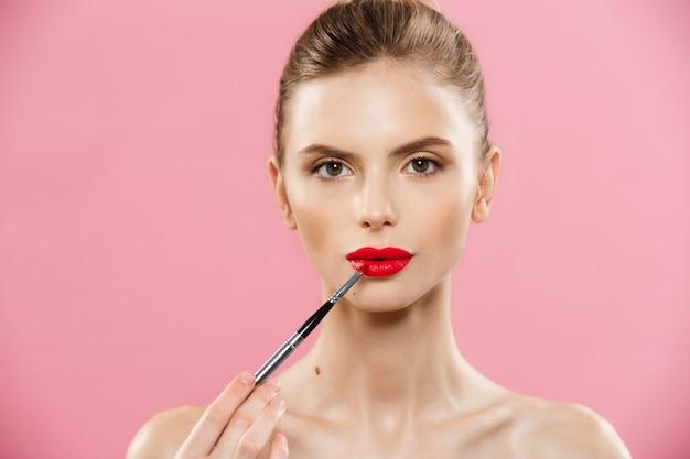 Conceito da beleza - mulher que aplica o batom vermelho com fundo cor-de-rosa do estúdio. menina bonita faz maquiagem.