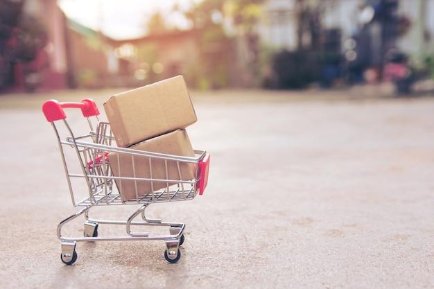 Conceito da compra: caixas ou caixas de papel no carrinho de compras no assoalho concreto. com cópia sp
