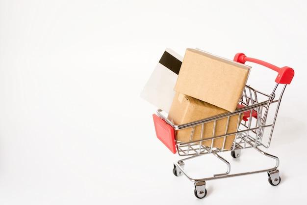 Conceito da compra: caixas ou caixas de papel no carrinho de compras vermelho no fundo branco. conectados