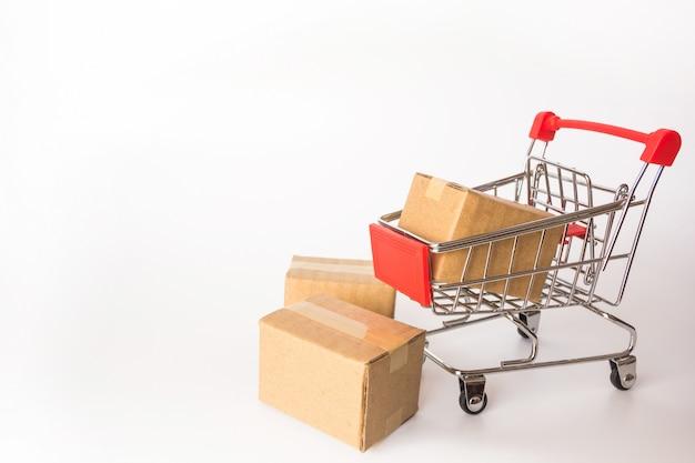 Conceito da compra: caixas ou caixas de papel no carrinho de compras vermelho no fundo branco.