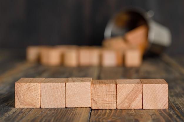 Conceito da estratégia empresarial com os cubos de madeira dispersados do balde na opinião lateral da tabela de madeira.