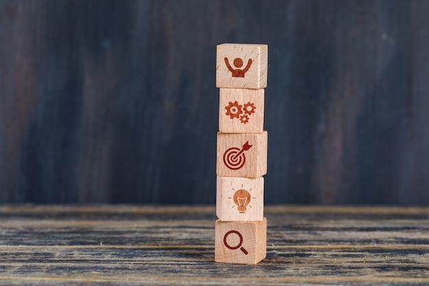 Conceito da estratégia empresarial com os cubos de madeira na opinião lateral do fundo de madeira e do grunge.