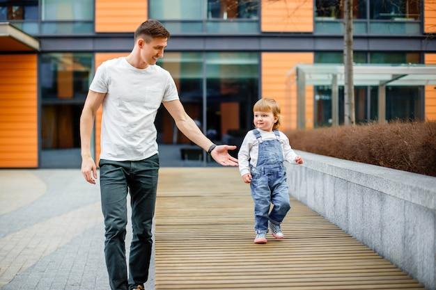 Conceito da família, da infância, da paternidade, do lazer e das pessoas - o pai novo feliz e a filha pequena dão uma volta pelas ruas da cidade