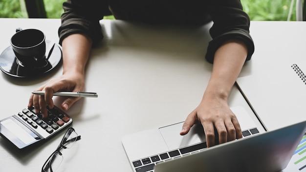 Conceito da finança do close up, calculadora de utilização fêmea e laptop na mesa de escritório.