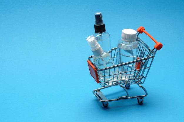 Conceito da higiene da proteção do vírus da corona - líquido do desinfetante da mão do álcool no troplley do carrinho de compras no fundo azul. . lavar à mão no cesto