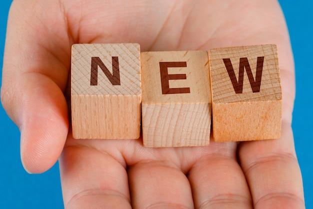 Conceito da ideia de negócio em close-up de mesa azul. mão segurando cubos de madeira com a palavra novo.