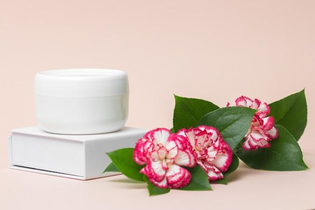 Conceito da indústria da beleza frasco de creme cosmético branco com flores