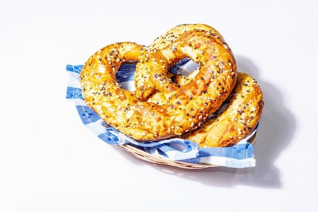 Conceito da oktoberfest - pretzels em um guardanapo tradicional, isolado no fundo branco. uma luz forte da moda, sombra escura, maquete