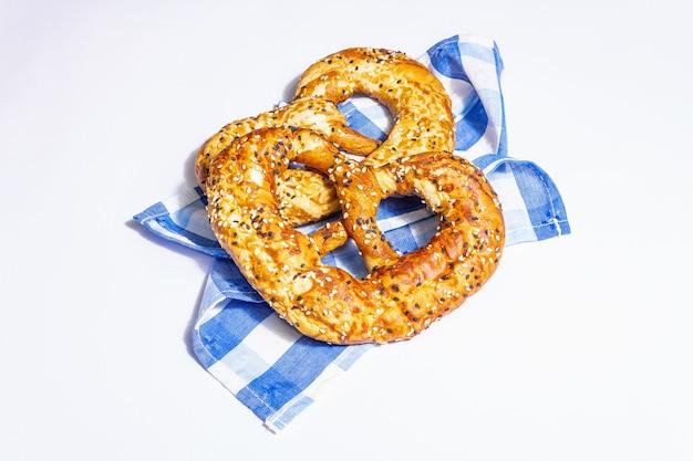 Conceito da oktoberfest - pretzels em um guardanapo tradicional, isolado no fundo branco. uma luz forte, sombra escura da moda