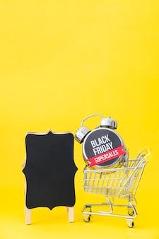 Conceito da sexta-feira negra com placa e despertador no carrinho