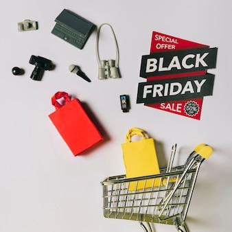 Conceito da sexta-feira negra com produtos, etiquetas e carrinho Foto gratuita