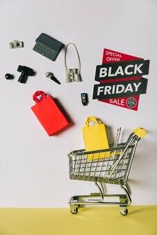 Conceito da sexta-feira preta com produtos que caem no carrinho Foto gratuita