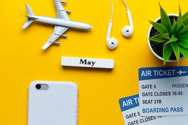 Conceito das férias de maio - brinque o avião com os bilhetes na parede amarela.