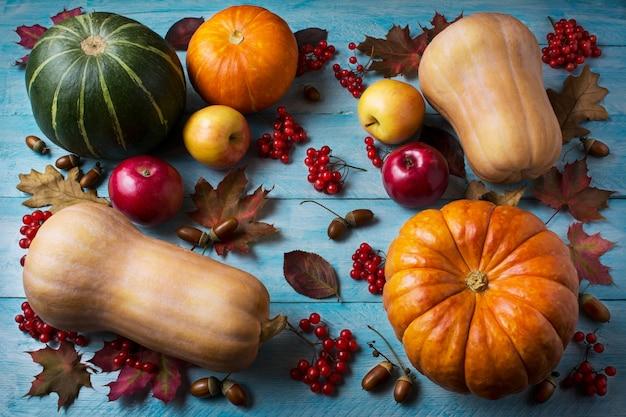 Conceito de ação de graças com abóboras e maçãs sobre fundo azul de madeira
