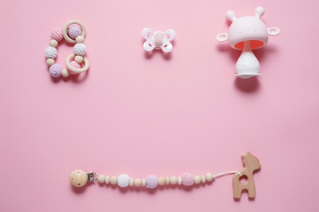 Conceito de acessórios para bebês: mordedor, brinquedo de lagarta e chupeta de bebê, sobre fundo rosa com espaço de cópia, vista superior, postura plana
