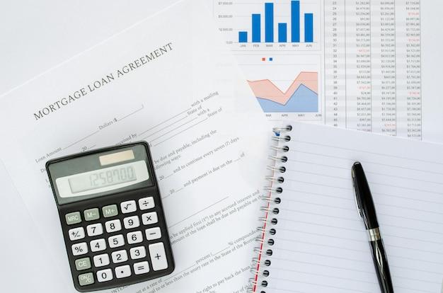 Conceito de acordo de empréstimo hipotecário com calculadora, bloco de notas, caneta e documentos financeiros. vista do topo.