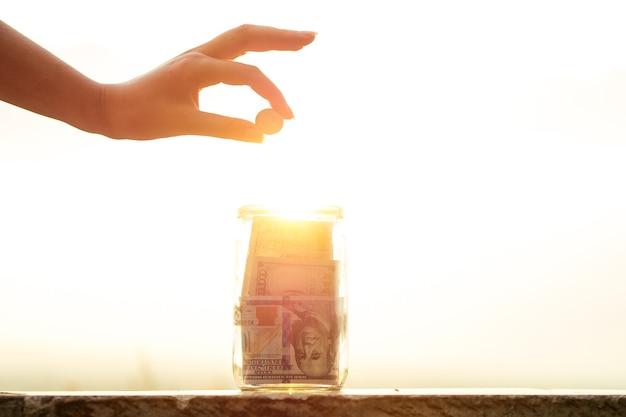 Conceito de acumular dinheiro em uma jarra de vidro sob a luz do sol com a ajuda do sol