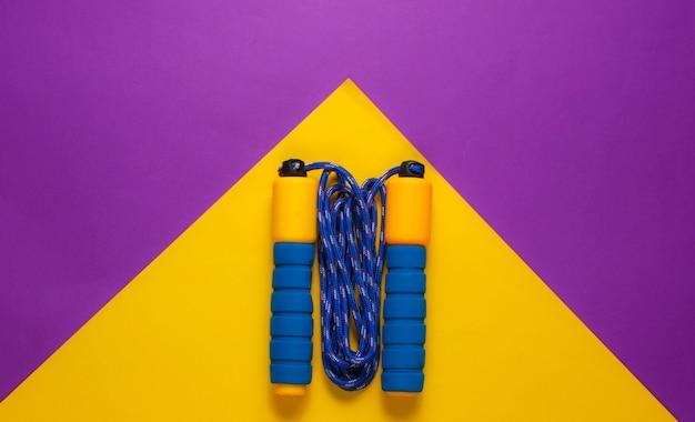 Conceito de adequação do minimalismo. pular corda em fundo amarelo roxo.