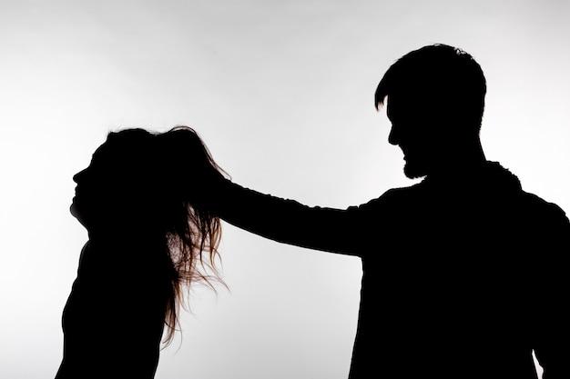 Conceito de agressão e abuso - homem e mulher expressando violência doméstica em silhueta de estúdio isolada no fundo branco.