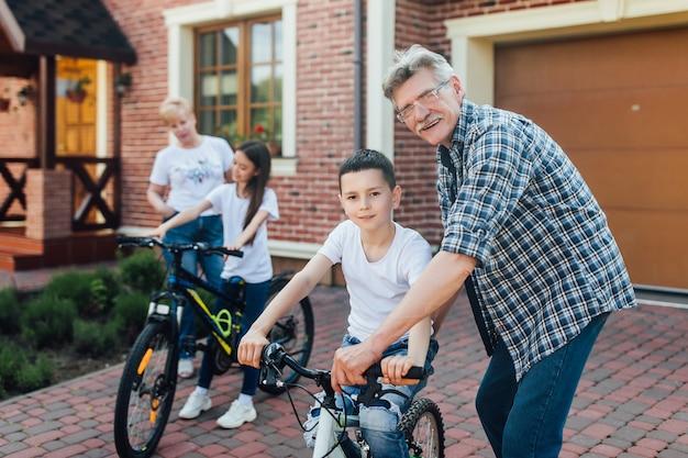 Conceito de ajuda, geração, segurança e pessoas - avô e menino felizes com bicicleta e bicicleta ensinam juntos.
