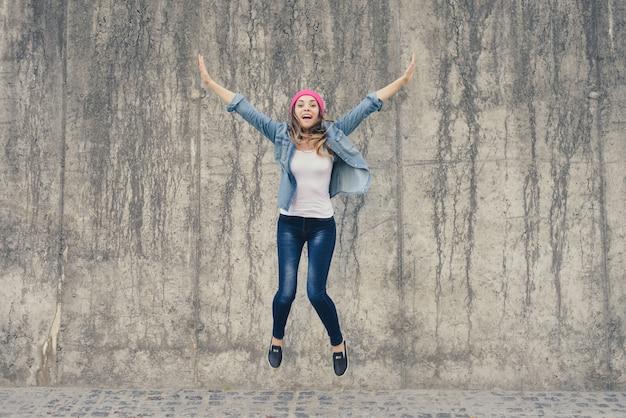Conceito de alegria e liberdade, vida sem problemas. garota louca e extremamente feliz em roupas jeans e chapéu rosa gritando e pulando com as mãos levantadas contra a parede cinza