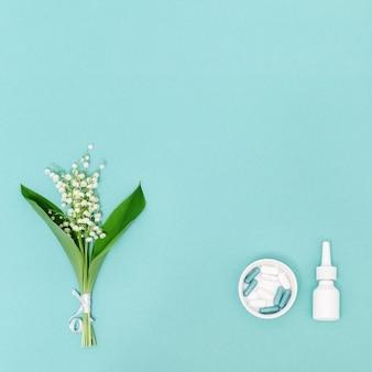 Conceito de alergias sazonais de primavera e verão à floração. spray nasal branco e comprimidos, flores perfumadas