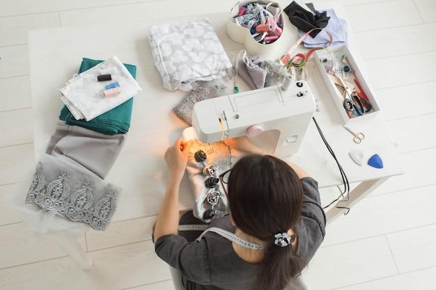 Conceito de alfaiate, moda e costureira - jovem designer de moda feminina em seu showroom, vista superior.