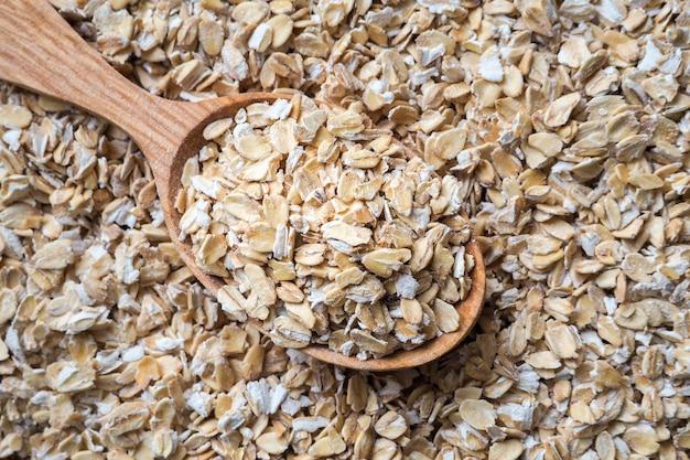 Conceito de alimentação saudável. aveia enrolada seca na tigela e colher.