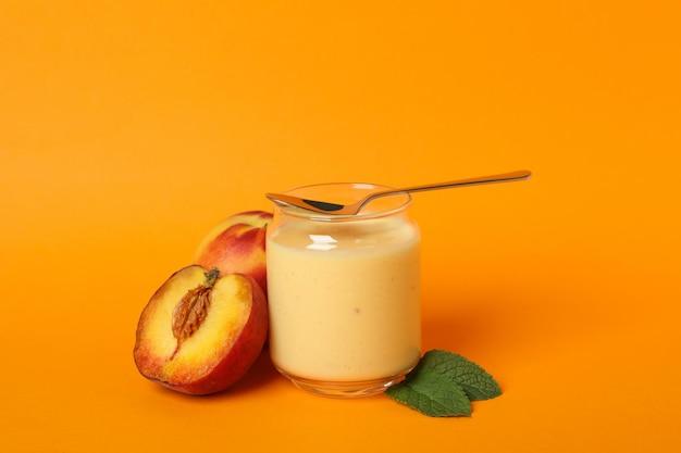 Conceito de alimentação saudável com iogurte de pêssego em fundo laranja