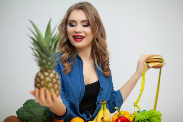 Conceito de alimentação saudável, hambúrguer com fita métrica amarela e abacaxi maduro.