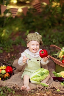 Conceito de alimentação saudável. menino na natureza recolhe uma colheita de legumes em um carrinho e prepara salada