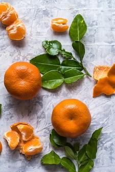Conceito de alimentação saudável. teste padrão com a tangerina fresca crua dos citrinos com folhas verdes.