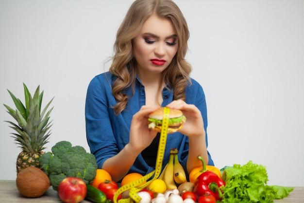 Conceito de alimentação saudável, uma mulher segurando um hambúrguer prejudicial.